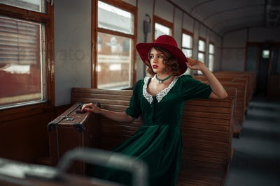 Beautiful woman in retro train, old wagon interior