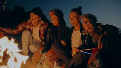 Happy hippie friends near bonfire