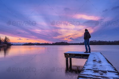 Man Looking at the Sunset From a Pier