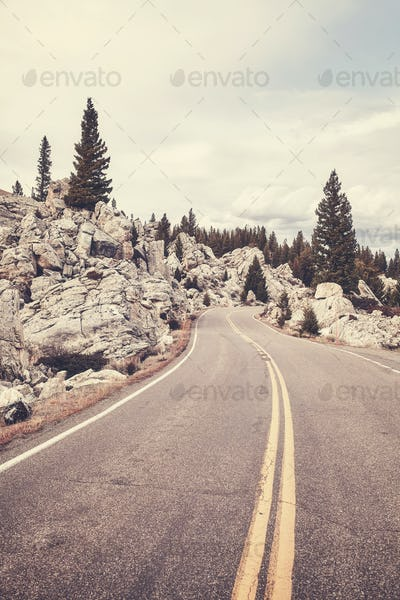 Vintage toned scenic mountain road in Yellowstone National Park.