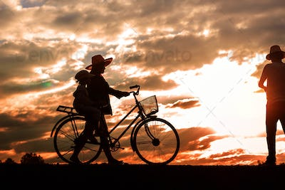 Parents with the bike at sunset