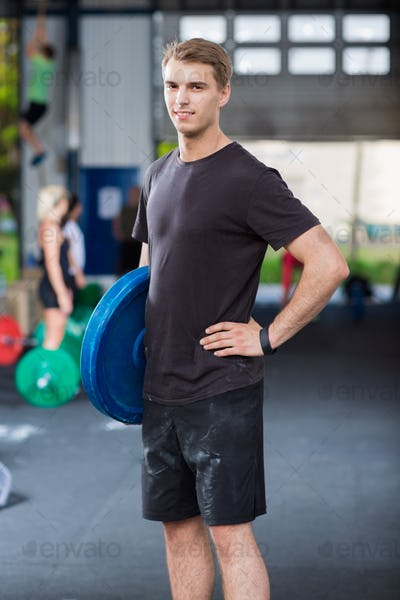 Confident Athlete Carrying Weight Plate In Warehouse