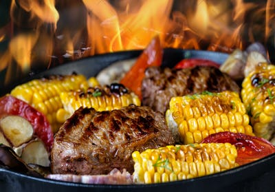 Fried meat and corn with vegetables in a frying pan on fire