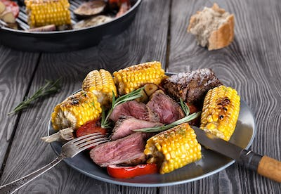 Fried meat and corn with vegetables on a plate