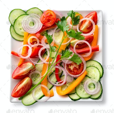 Salad of sliced raw fresh vegetables on white plate