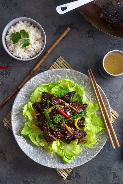 Asian stir fried chicken liver with bowl of rice and green tea