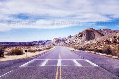 Vintage toned picture of a scenic deserted road.