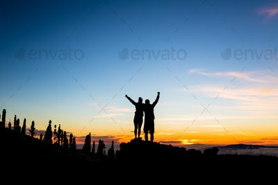 Teamwork couple climbing and reaching mountain peak