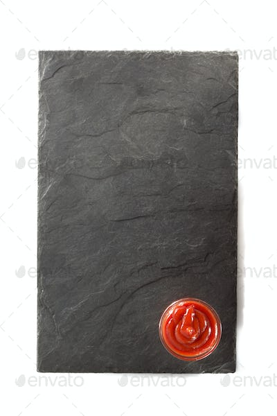 black slate and ketchup isolated on white