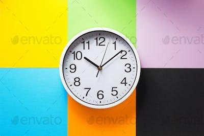 wall clock at abstract colorful paper
