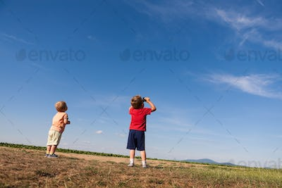Back side of two boys looking at the sky