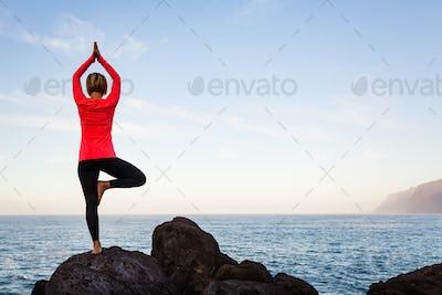 Woman meditating in yoga vrksasana tree pose