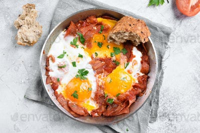 Fried eggs with bacon in frying pan