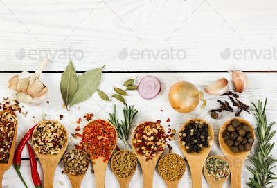 Different spices in wooden spoon. Top view.