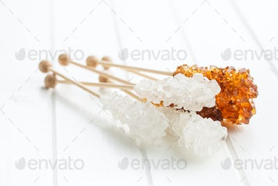Crystalline sugar on wooden stick.