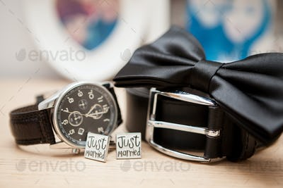 Shirt buttons, belt, watch and bow on a table