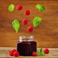 raspberry jam with flying mint and fresh raspberries