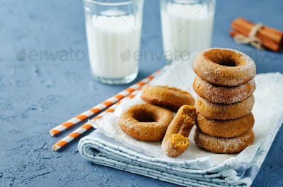 Baked pumpkin donuts with glasses of milk