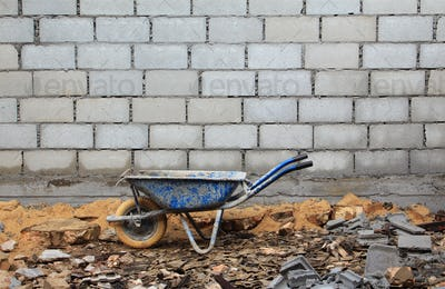 Old rusty wheelbarrow in construction site