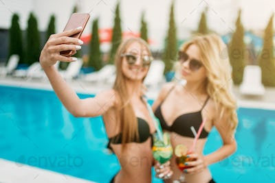 Two sexy girls makes selfie near the swimmimg pool