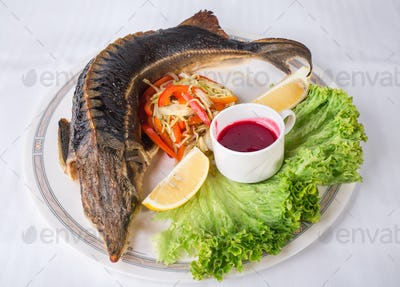Baked sturgeon with vegetables.