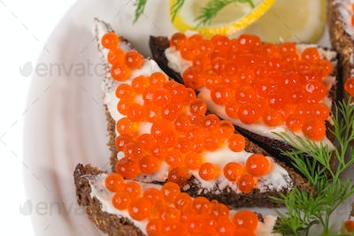 Rye bread with butter and red caviar.