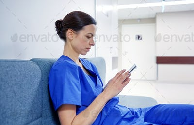 female doctor or nurse with smartphone at hospital