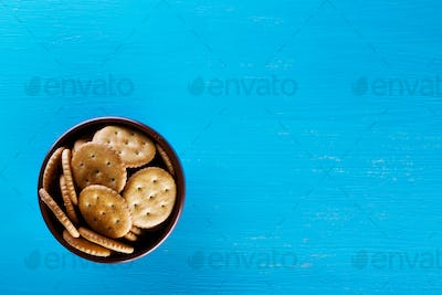 Bowl with crispy crackers on blue background