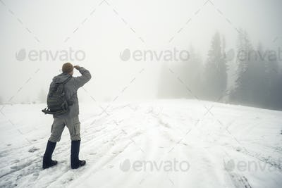 Man with backpack in the winter mountains peers into the foggy d