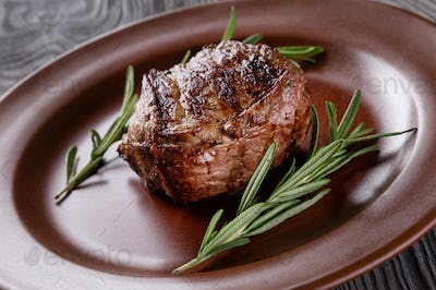 Fried meat on a plate with rosemary