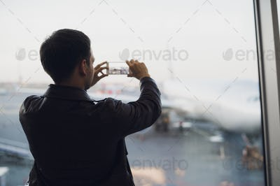 Man hand take picture of airplane using cellphone. Tourism concept photo