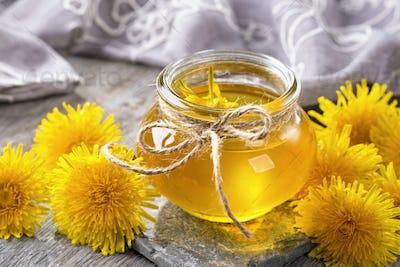 Dandelion honey in a jar and fresh flowers