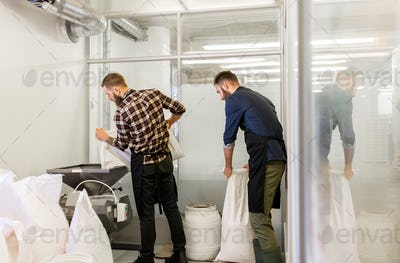 men with malt bags and mill at craft beer brewery