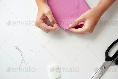 woman with pins stitching paper pattern to fabric