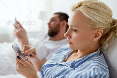 couple with smartphones in bed at home