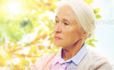 senior woman face over green natural background