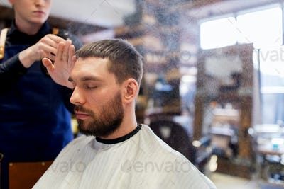 barber applying styling spray to male hair