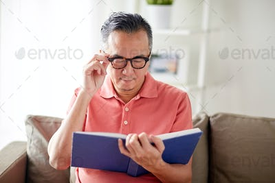 man in glasses reading book at home