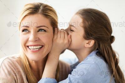 happy girl whispering secret to her mother