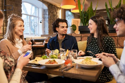 friends with smartphones eating at restaurant