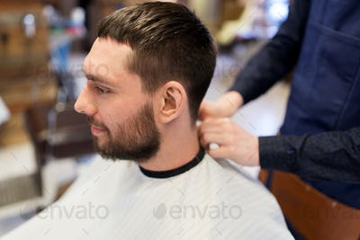 hairdresser and man with beard at barbershop