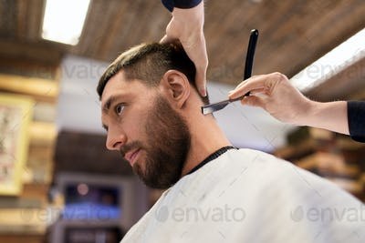 man and barber with straight razor shaving hair