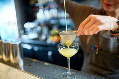 bartender pouring cocktail into glass at bar