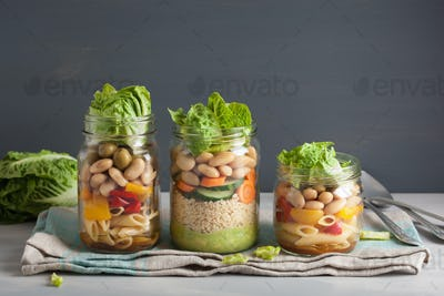vegan couscous and pasta salad in mason jars with vegetables bea