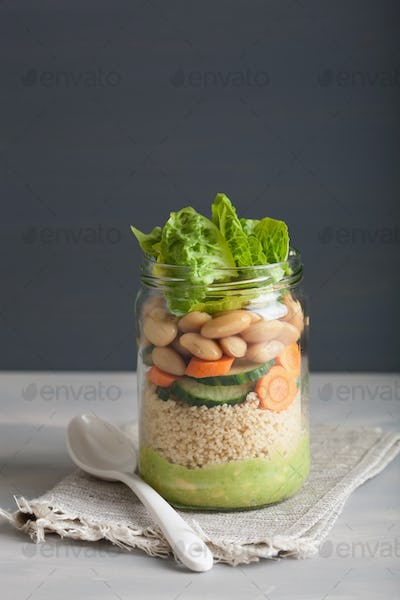 vegan couscous salad in mason jar with beans cucumber carrot and