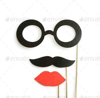 fake lips, glasses and mustaches on sticks