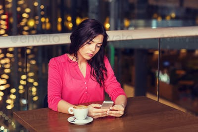 woman with smartphone and coffee at restaurant