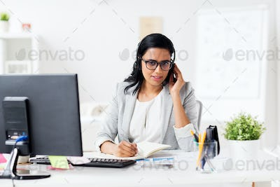 businesswoman with headset and notebook at office