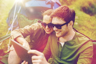 happy couple with tablet pc at camping tent