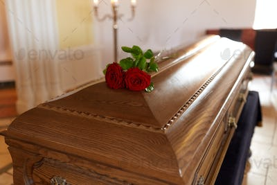 red rose flowers on wooden coffin in church